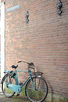 Blauwe herenfiets met voordrager tegen muur Delft van Mariska van Vondelen
