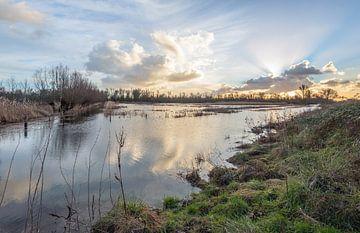 Crepusculaire zonnestralen aan een bewolkte hemel van Ruud Morijn
