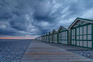 Strandhuisjes tijdens zonsondergang en onweerswolken.