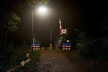Nachtopname van een beveiligde overweg van Jenco van Zalk
