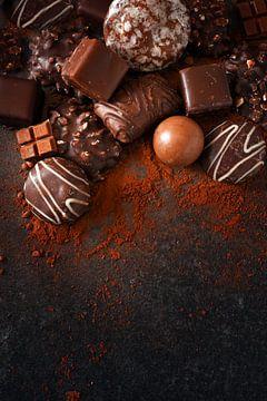 feestelijke chocoladekoekjes en pralines op een leisteenplaat, donkere achtergrond met royale kopiee van Maren Winter