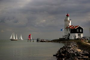 """Red and white sailing ships sail along """"Het Paard"""" / the lighthouse in Marken.,"""