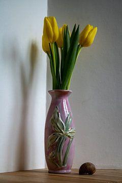 Frische gelbe Tulpen in einer schlanken rosa Vase von Susan Hol