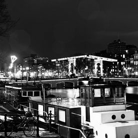 De Amstel brug met boten in Amsterdam  zwart-wit van Dexter Reijsmeijer