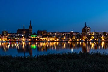 Uitzicht over de rivier de Warnow naar de Hanzestad Rostock bij nacht van Rico Ködder