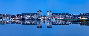 Panoramablick auf Mehrfamilienhäuser, die sich in einem Kanal spiegeln von Tony Vingerhoets