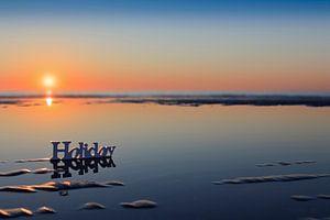 zonsondergang achter het woord Holiday op het strand