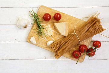 keukenbord met ingrediënten voor een Italiaanse maaltijd van bovenaf gezien met volkoren spaghetti,  van Maren Winter