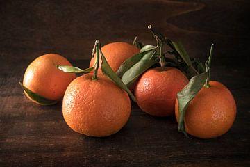 verse clementinevruchten met bladeren op een donkere rustieke houten achtergrond, geselecteerde focu van Maren Winter
