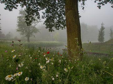 Mist, bloemen en een boom van