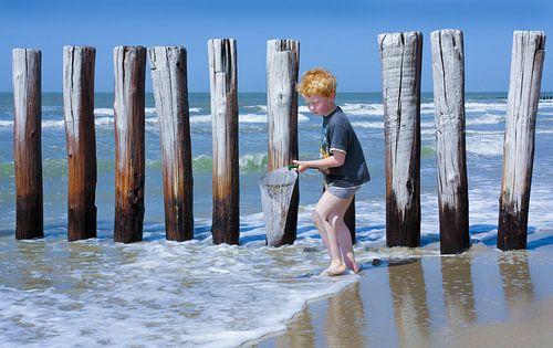 Vissend jongetje op het strand van Badzand, Zeeland.