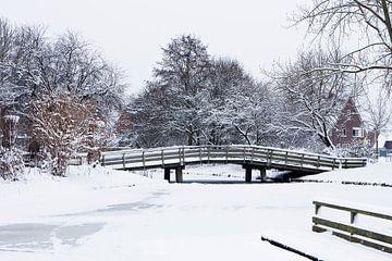 Houten fietsbrug in een besneeuwd landschap von Bert Meijerink
