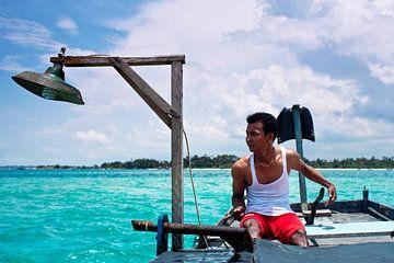 Jonge kapitein kijkt over blauwe, tropische Indonesische zee van André van Bel