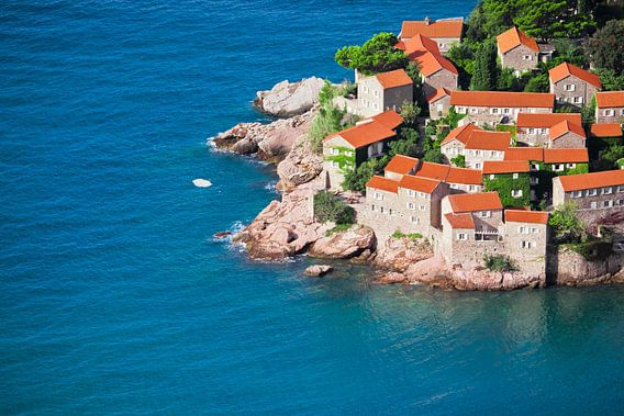 Mediterrane stad. kleine huizen met een pannendak en groene bomen aan de blauwe zee. geluk in ontspa