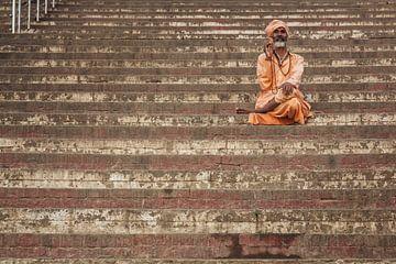 man rust op stappen van een ghat in Varanasi, India. van Tjeerd Kruse