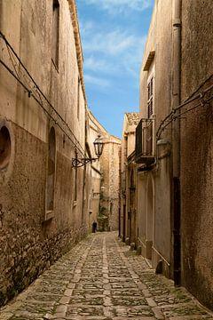 Nauw straatje  met kasseien in Erice, een middeleeuws stadje, Sicilië, Italië van Mieneke Andeweg-van Rijn
