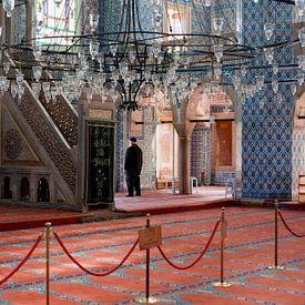 Man in gebed, Moskee in Istanbul, Turkije, met prachtige blauwe tegels en rood tapijt. van Eyesmile Photography