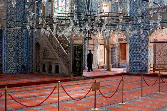 Man in gebed, Moskee in Istanbul, Turkije, met prachtige blauwe tegels en rood tapijt.