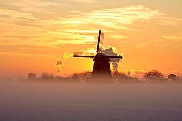 Traditionele hollandse molen in de winter bij zonsondergang van
