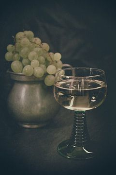 Ein Glas Weißwein mit hellen Weintrauben im Hintergrund von Edith Albuschat