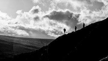 drei Männer auf dem Bergrücken im schwachen Abendlicht von Studio de Waay