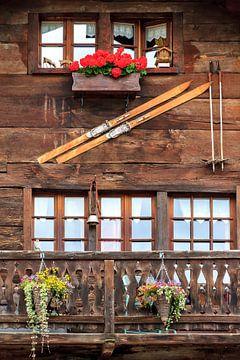 Skies aan de muur en geraniums op het balkon in Zwitserland sur Dennis van de Water