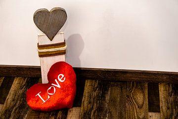 Ein Rotes Stoff Herz liegt vor einem Herz aus Holz von Tom Voelz