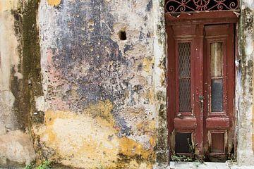 Donkerrode oude vervallen deur naast oude muur van Yke de Vos
