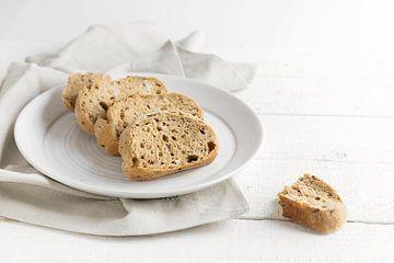 pain complet frais dans une assiette, sur une table en bois rustique peinte en blanc, espace de copi sur Maren Winter