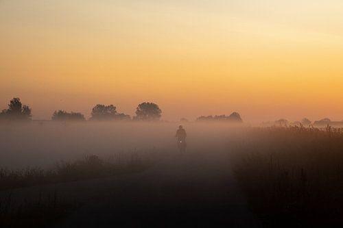 Fietsen naar het werk door de mist