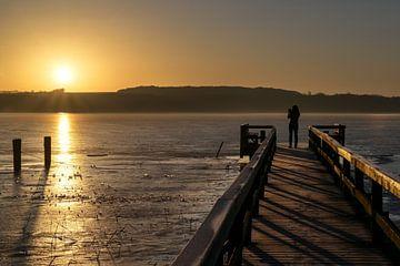Jeune femme de dos en silhouette sur une jetée en bois prenant une photo du soleil levant sur le lac