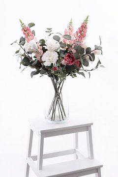 Vase mit schönen weißen und rosa Blumen auf einer weißen Treppe