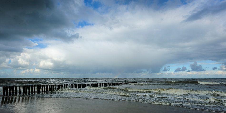 Dreigende Lucht met Regenboog boven Kalme Zee (1)