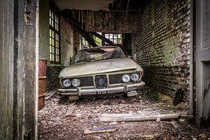 Oude auto in vervallen garage van