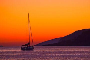 Segelyacht im warmen tropischen Meer unter einem leuchtend orangenen Sonnenuntergang geparkt, Entspa von Michael Semenov