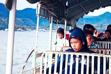 Indonesische schooljongen op de veerpont kijkt nadenkend in de verte van André van Bel
