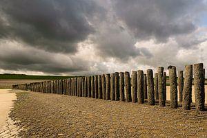 Strandhoofd met donkere, dreigende wolken