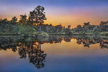 Rustig meer bij zonsondergang met oranje gekleurde hemel van Tony Vingerhoets
