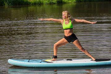 Junge europäische Frau, die Yoga auf SUP auf dem Wasser praktiziert. von Ben Schonewille