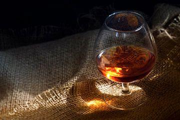 Cognac of brandewijn in een glas met een gloeiende lichtreflex op rustieke jute, concept voor genot  van Maren Winter
