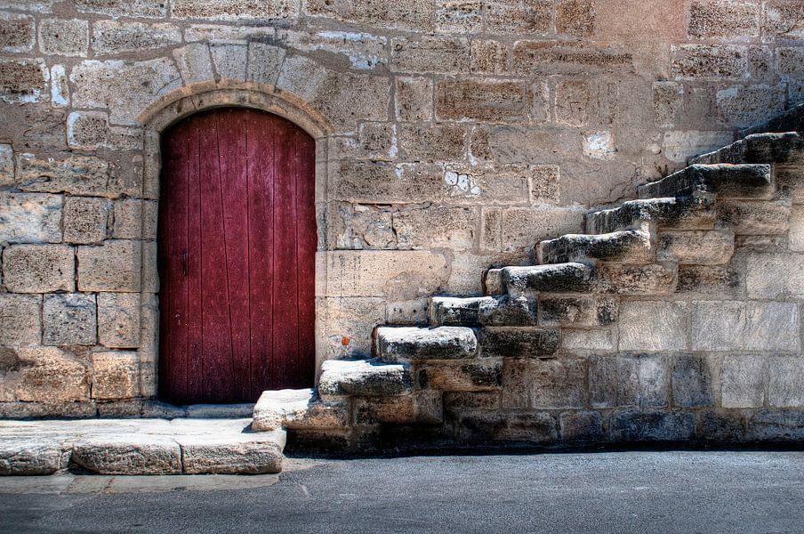 Oude stadsmuur met rode deur en trap