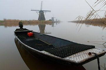 bootje en molen Kinderdijk in de mist van Merijn Loch