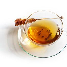 Tasse en verre à moitié remplie de thé noir et d'un bâton de sucre candi avec une ombre réfléchissan sur Maren Winter