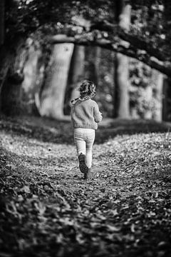 Zwart-wit foto van rennend meisje met vlechtjes op bos pad