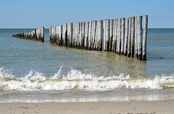 Strand met branding en palen in de zee van Trinet Uzun