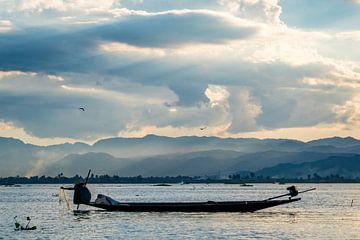 Visser haalt zijn netten op tijdens zonsondergang op het Inle meer in Myanmar. van Twan Bankers