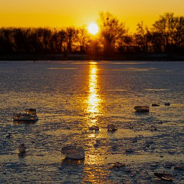 Stuk ijs op een bevroren meer tijdens een warme zonsopkomst van Kim Willems