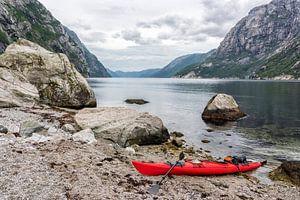 Uitzicht in het  Lysefjord met een rode kajak in Noorwegen tijdens een kanotocht in de zomer