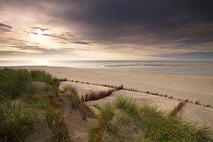 Zonsondergang op een bewolkte dag aan de Nederlandse kust