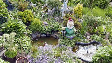 Kitscherige tuinkabouter en stenen ezeltje  in burgerlijk tuintje met vijver van Gert Bunt